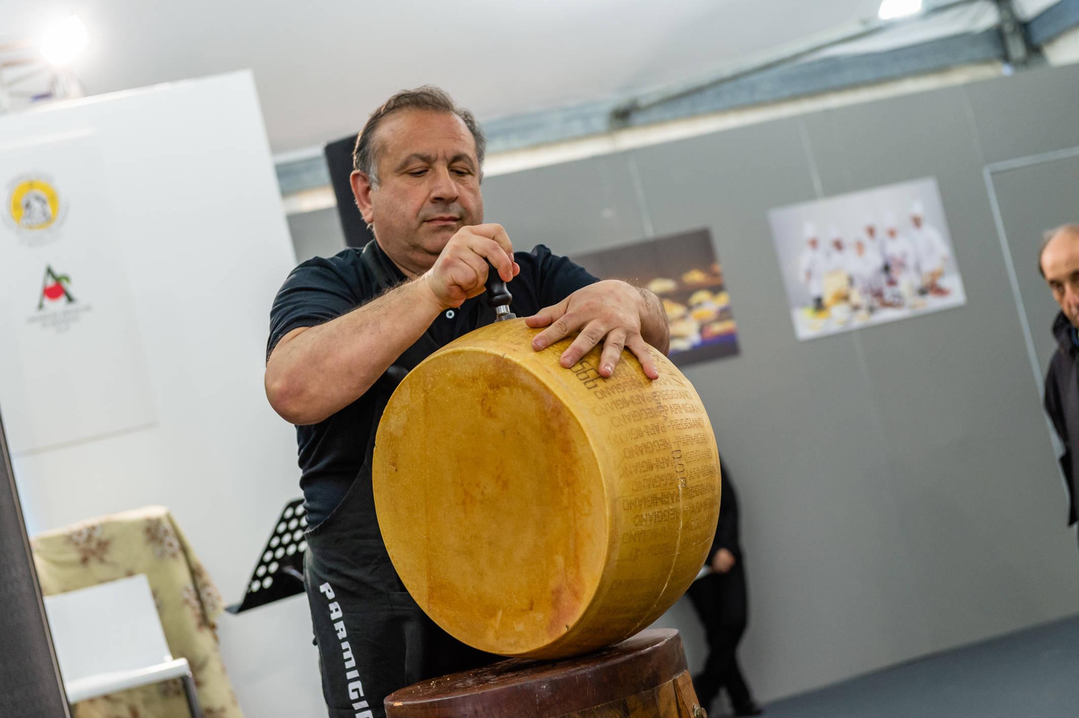 I mestieri del gusto al Motor Valley Fest: l'apertura di una forma di Parmigiano Reggiano.